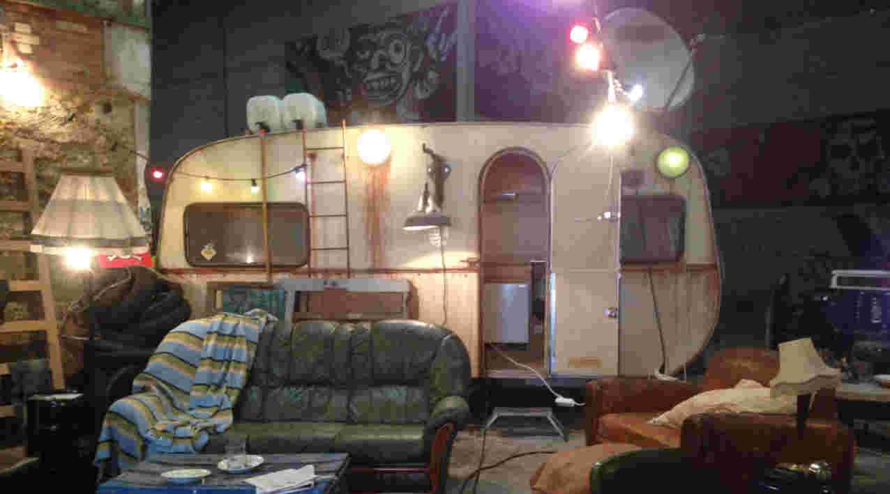 décor de squat avec caravane et fauteuil dans une usine désaffectée pour la série télévisée José